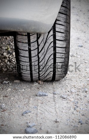 Close up of a car tire on a dirty road. Gritty look and vignetting on the corners of the image - stock photo