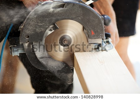 Close-up of a carpenter using a circular saw to cut a large board of wood - stock photo
