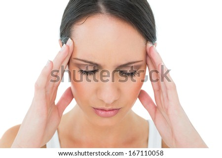 Close-up of a casual young woman suffering from headache over white background - stock photo