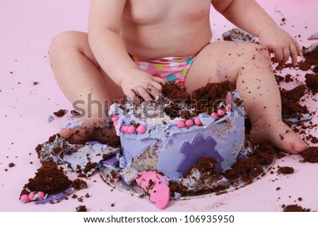 Close up of a caucasian birthday girls legs and arms while she destroys and smashes her chocolate birthday cake with pink and purple butter icing getting the sticky icing all over her fingers and toes