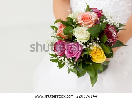Close up of a caucasian bride holding flowers. - stock photo