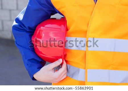 Close-up of a caucasian man holding a red hardhat against a white background - stock photo