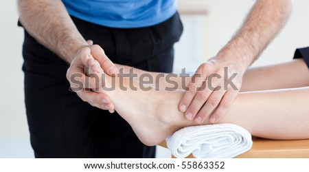 Close-up of a Caucasian physical therapist giving a foot massage in a health center - stock photo