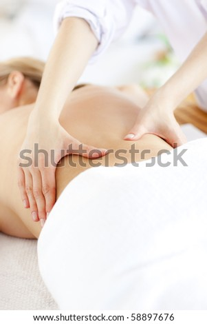 Close-up of a caucasian woman receiving a back massage in a spa center - stock photo