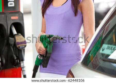 Close-up of a caucasian woman refueling her car in a service station - stock photo