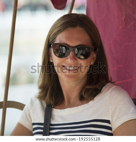 Close-up of a caucasian woman wearing sun glasses and smiling, Hutong, Beijing, China - stock photo