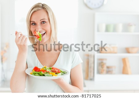 Close up of a charming woman enjoying mixed salad in kitchen