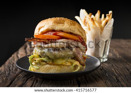 Close Up of a cheese burger with fresh toppings on bread bun. Gourmet burger with fries on a rustic wooden table and dark background.