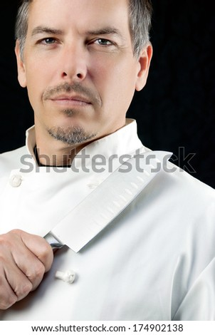 Close-up of a chef displaying his knife, portrait. - stock photo