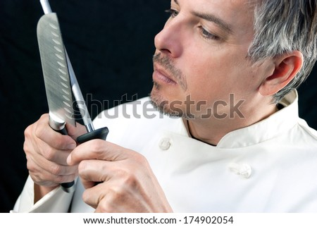 Close-up of a chef sharpening his knife. - stock photo
