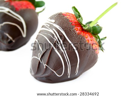 Close up of a chocolate covered strawberry on a white background with another strawberry out of focus in the back. Used a shallow depth of field and selective focus. - stock photo