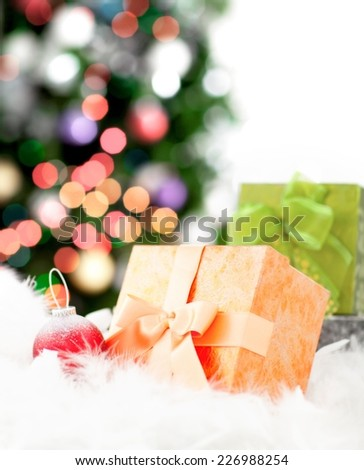 Close up of a Christmas tree decoration and gift box - woman decorating christmas tree in the background - stock photo