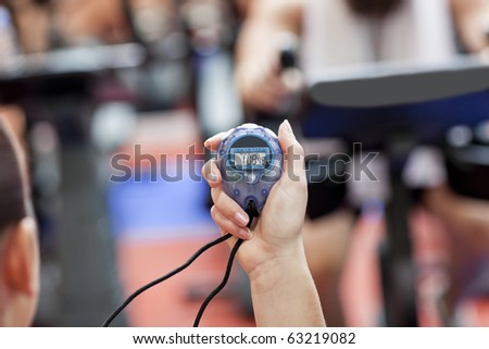 Close-up of a chronometer holding by a female coach in a sport centre - stock photo