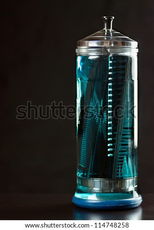 Close-up of a clear glass container of disinfectant full of combs. - stock photo