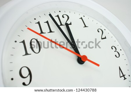 close up of a clock face showing the hands at two minutes to midnight - stock photo