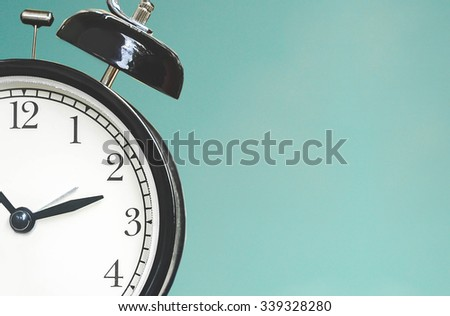 Close up of a clock isolated on blue background with copy space - stock photo