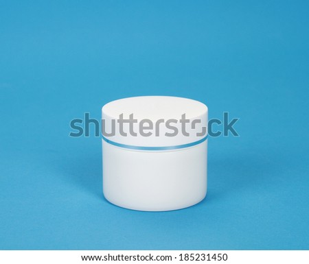 close up of a closed beauty cream or yogurt on blue background - stock photo