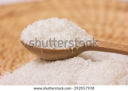 Close up of a coconut and grounded coconut flakes - stock photo