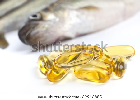 Close up of a  cod liver fish oil capsule, a nutritional supplement high in omega-3 fatty acids, EPA,  DHA, and  high levels of vitamin A and vitamin D.  Fresh fish are in the background. - stock photo