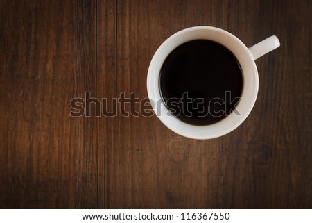 Close up of a coffee mug on a dark wooden table. Shot from above. - stock photo