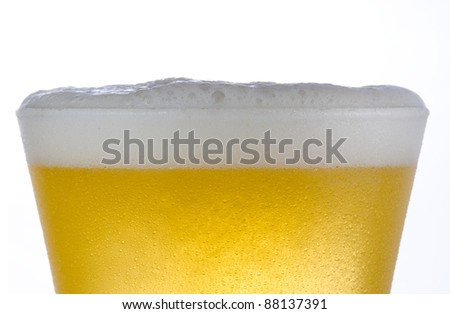 Close up of a cold frosted pilsner beer glass with light beer and head just above rim level