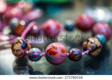 Close-up of a colorful necklace on a glass table - stock photo