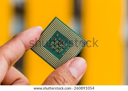 Close-up of a computer processor microchip between the fingers in hand - stock photo