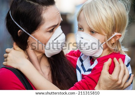 Close-up of a  concerned woman looking at her sick son. Both are wearing protective face masks for pollution or virus. - stock photo