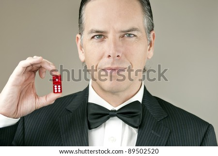 Close-up of a confident gentleman in a tux holding a pair of red dice showing seven.