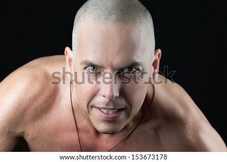Close-up of a confident man looking to camera, shirtless, shaved head - stock photo