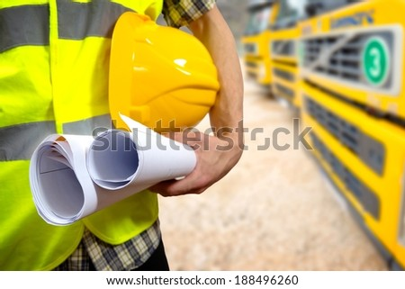 Close up of a construction worker's hand holding project documents and hat. - stock photo