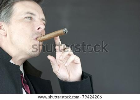 Close-up of a contemplative businessman smoking a cigar. - stock photo