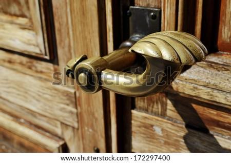 close-up of a copper doorknob and wood door - stock photo