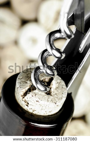 Close-up of a corkscrew opening a wine bottle on corks background