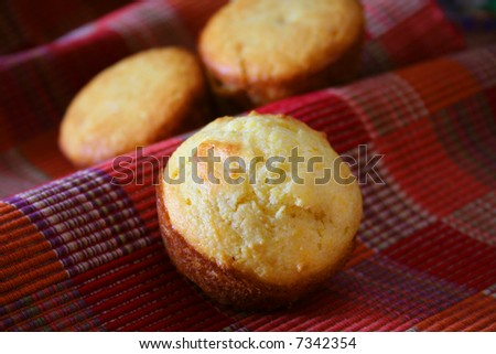 Close up of a cornbread muffin, with two muffins in the background. - stock photo