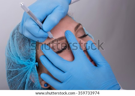 Close up of a cosmetologist applying a special permanent make up on a  woman's eyebrows. - stock photo