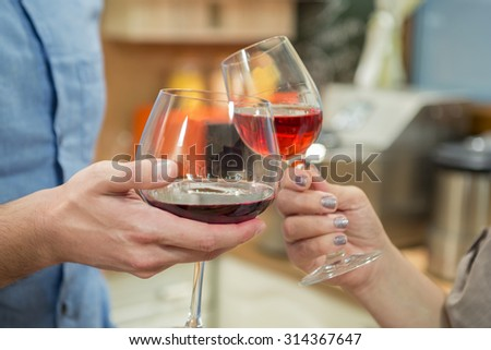 Close up of a couple celebrating and toasting with red wine. Toasting with wineglasses.
