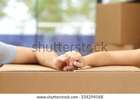 Close up of a couple holding hands over a carton box and moving home - stock photo