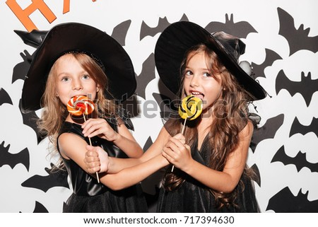 Close up of a couple of two cute little girls dressed in halloween costumes eating lollipops  sc 1 st  Shutterstock : cute girl couple halloween costumes  - Germanpascual.Com