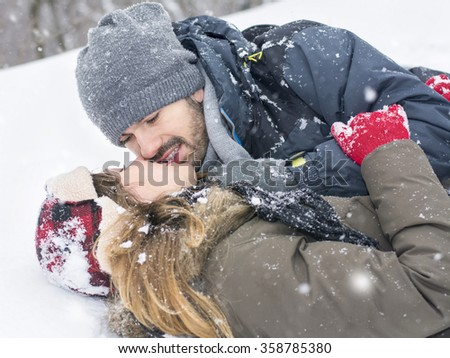 Close up of a couple on a winter day kissing on the snow - stock photo
