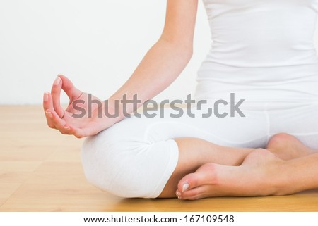 Close-up of a cropped toned woman in lotus pose at a fitness studio - stock photo