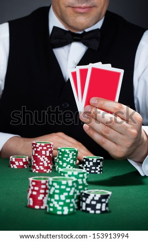 Close-up of a croupier holding playing cards - stock photo