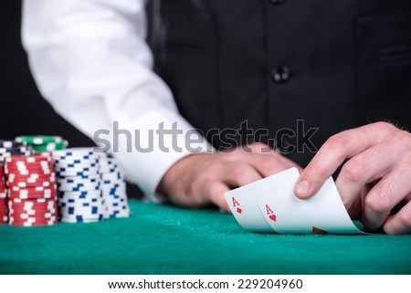 Close-up of a croupiers hand is holding gambling cards on table.