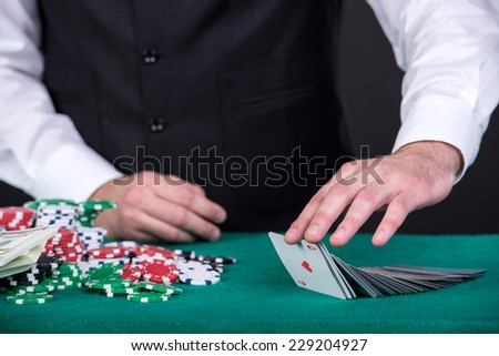 Close-up of a croupiers hand with  gambling cards and chips on the table.