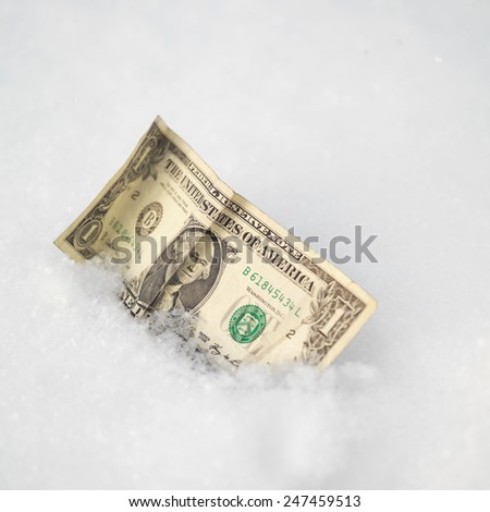 Close up of a crumpled dollar bill in a snow, lost and found  concept
