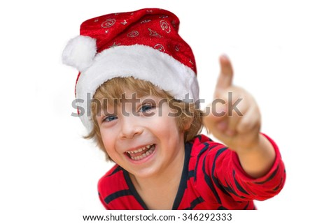 Close-up of a cute little boy with Santa, red shirt, smiling happily and pointing isolated on white background