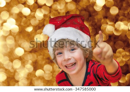 Close-up of a cute little boy with Santa, red shirt, smiling happily and pointing, on golden sparkling background