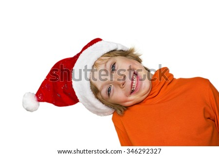 Close-up of a cute little boy with Santa, smiling, head sideways,  looking around the corner isolated on white background
