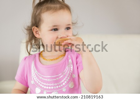 Close up of a cute little girl eating biscuit at home