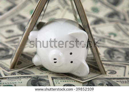 Close up of a cute Piggy Bank under shelter of cash. Shallow depth of field. Lying down to signify sleep, peaceful, or fallen. - stock photo